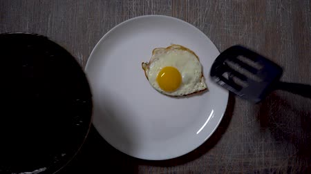 cuisine dark : Top view of fried eggs eating with fork and knife. Traditional breakfast eggs eating. Morning breakfast service Stock Footage