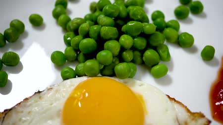 omlet : 4k scrambled eggs on a white plate with peas and sauce. Top view of fried eggs eating with fork and knife. Traditional breakfast eggs eating. Morning breakfast service