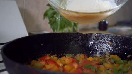 chives : Slow motion, Dinner from eggs and red pepper is cooked in a frying pan. A beautiful dinner of eggs of greenery and bell pepper,traditional Spanish tortilla made from eggs,onions and potatoes. Stock Footage