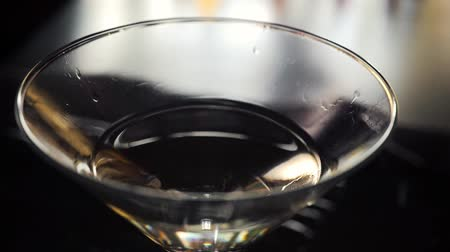 vermouth : Slow motion shot of olive splashing into martini. Green olive is falling into a glass of Dry Martini cocktail.