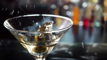 sıçrama : Slow motion shot of olive splashing into martini. Green olive is falling into a glass of Dry Martini cocktail.