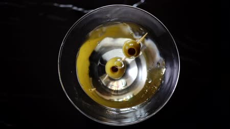 Slow motion shot of olive splashing into martini. Green olive is falling into a glass of Dry Martini cocktail.