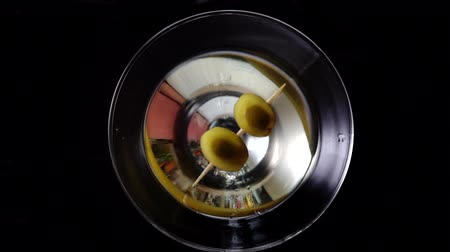 pálinka : Slow motion shot of olive splashing into martini. Green olive is falling into a glass of Dry Martini cocktail.