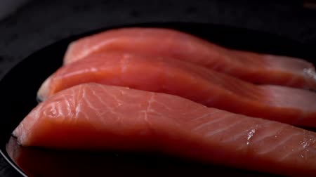 Raw salmon fillet on a slate board. Raw salmon red fish. HD, Slow motion, Cooking salmon, seafood. Healthy food concept. Vídeos