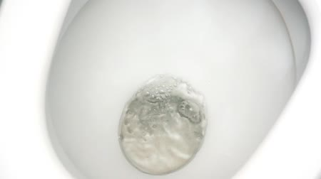 Morning starts not with a coffee. Closeup video of a flushing white toilet.