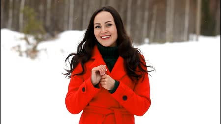 Happy young woman in red coat posing in winter forest and sending you a kiss