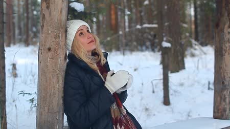 Pretty woman drinking hot tea or coffee in a winter forest Stok Video