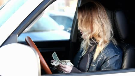 young woman counts money in the car