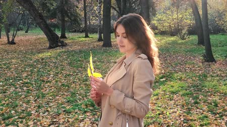 Pretty woman with a leaf in autumn park