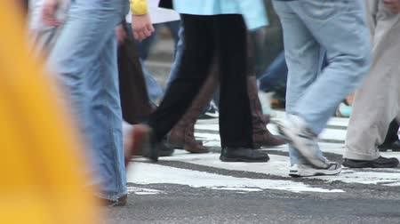 encruzilhada : Busy New York traffic passing in front of the feet of a crowd of pedestrians crossing the street at a crosswalk Stock Footage