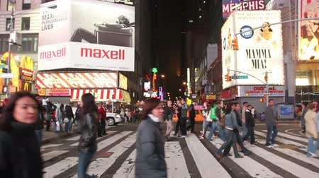 cruzamento : People crossing the street at an intersection in Times Square, New York at night. Includes audio.