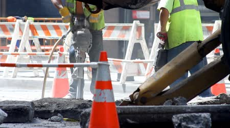 road construction : Two construction workers operating jackhammers on a city street