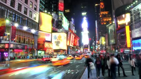 čas : Time lapse with busy street and sidewalk in Times Square at night, with blurringobscuring of signs and people.