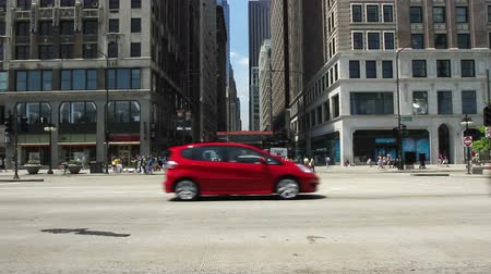 в центре города : Looking across a street in the City of Chicago, with traffic passing in front of camera.