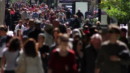 lento : Telephoto shot with a backlit crowd of people on a wide sidewalk, walking in slow motion