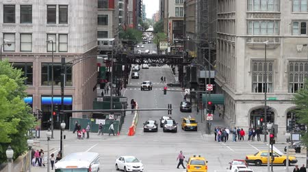 el train : High angle of a Michigan Avenue intersection and the border of The Loop in Chicago, with traffic, pedestrians, and en el train passing by.