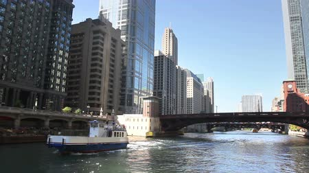 pomost : View from a boat as it passes underneath a bridge and passes another boat on the Chicago River in the middle of downtown Chicago.