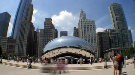 в центре города : Low angle time lapse of tourists crowding the Cloud Gate sculpture in Millennium Park in the city of Chicago, with skyscrapers in the background. You or may not see from the preview - this clip has some blurring on the edges as a result of the fish-eye le