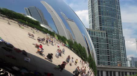 rzeźba : Tourists exploring Millennium Park in the reflection of the Cloud Gate sculpture, with the Chicago skyline.
