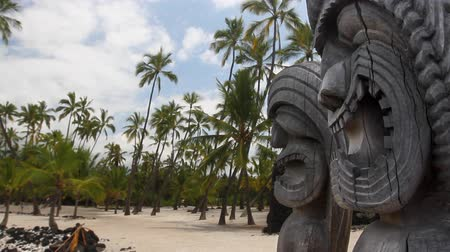 статуя : Hawaiian Tikis in the foreground with a sandy palm tree beach in the background
