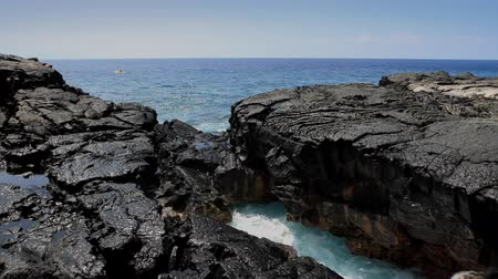 hardened lava : Ocean water splashes out from under a natural arch formed from volcanic rock in Hawaii. A Kayaker rows by in the background