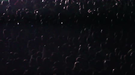 концерт : Spotlights illuminate sections of a crowd of cheering fans at a rock concert. Стоковые видеозаписи