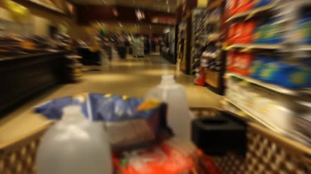 corredor : Time Lapse of shopping cart moving through the aisles of a supermarket, filling with items Vídeos