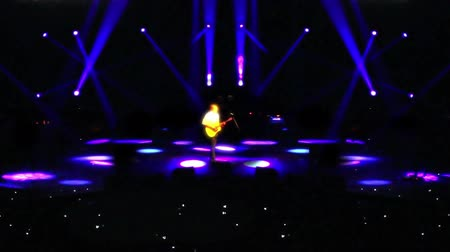 rockstar : An anonymous man plays the guitar on a darkened stage under the spotlights in front of a crowd