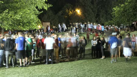 event : Time lapse of a crowd of teenagers socializing in a park at night.