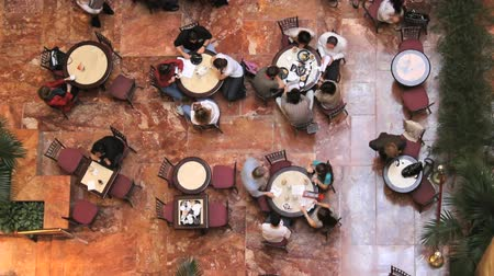 ülő : A time lapse shot and a real time shot, of a busy indoor cafe from a high angle