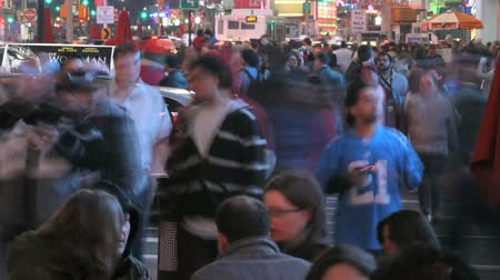 zaman : Time lapse of a crowd of people exploring Times Square at night with motion blur
