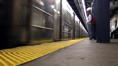 slowing : A woman waits as the subway train arrives at the station