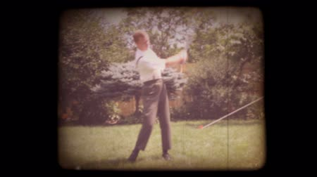 égés : 1950s home movie of a man trying out a golf club in his yard with a vintage 8mm film look. Shots are recent, but very authentic looking. Includes projector audio.