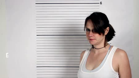 przestępca : Police mug shots of a female criminal holding a placard, standing in front of a white rulered wall.