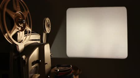 царапина : An antique 8mm film projector is turned on in a dark room, and projects a blank movie with a dust and hair texture, lifted from real 8mm film. Includes projector audio. Стоковые видеозаписи