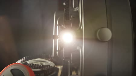Includes two shots. Looking into the lens of an antique 8mm film projector as it is turned on and projecting beams of light. Includes projector audio.