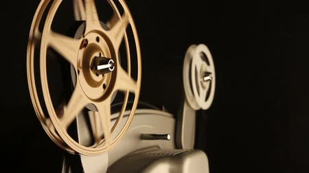 filmes : Close-up on the spinning film reels of an antique 8mm film projector in a dark room. Includes projector audio