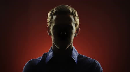 тайна : A businessman, whose face is hidden in shadow, stares into the camera in front of a red background. Off-centered version also available. Стоковые видеозаписи