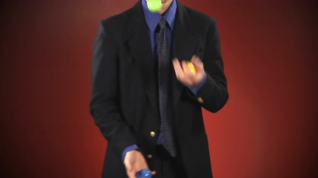 bolas : An anonymous businessman in a suit juggles 3 balls in front of a red background. Off-centered version also available.