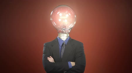 düşünürken : A man in a suit with a light bulb in place of a head steps into frame, taps the bulb, and a light flickers on. Off-centered version also available. Stok Video
