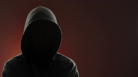 mroczne : An anonymous, threatening thug wearing a hood stares at the camera in front of a red background. Centered version also available.