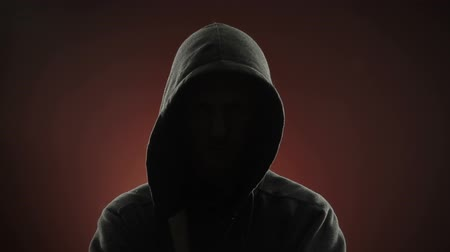 maska : An anonymous, threatening thug wearing a hood stares at the camera in front of a red background. Off-centered version also available.