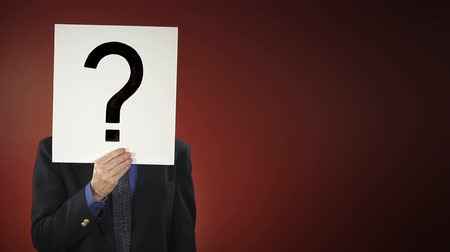 tajemnica : A businessman steps into frame holding a sign with a question mark in front of his face. Centered version also available.