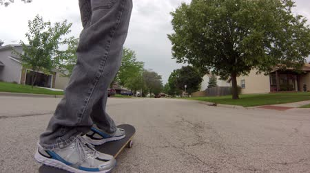Low angle tracking shot, following a skater skateboarding down the street.
