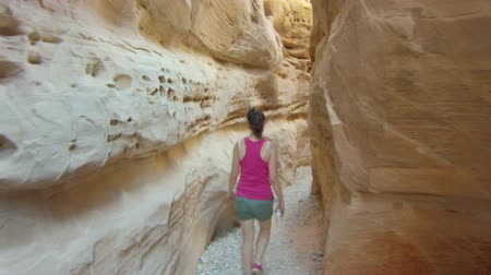 Following a woman hiking through a narrow desert canyon in Valley of Fire National Park, then tilting upward to reveal the sky and sun Dostupné videozáznamy