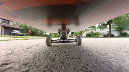 POV shot from under a skateboard as a person skates down the street.