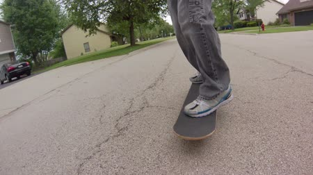 Low angle tracking shot, in front of a skater skateboarding down the street.