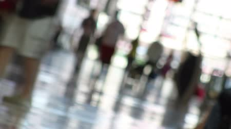 Canted, out-of-focus, time lapse shot of people with luggage, walking down the check-in hall of an airport.