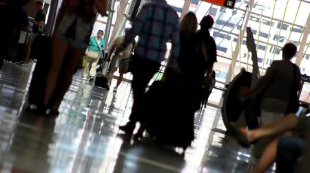 Canted shot of people with luggage, walking down the check-in hall of an airport.