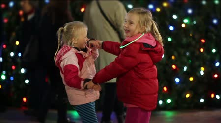 o : Slow motion - Two young children sisters dance together in front of a Christmas tree at night at a Christmas festival